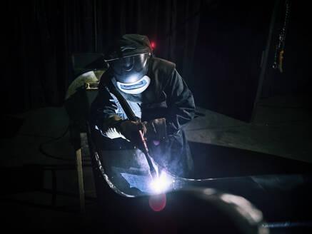 Industriefotografie (mit Relaese) Arbeiter mit Schweißhelm und Arbeitskleidung bei Schweißarbeiten, Kundl, Tirol, Austria - CVF01235
