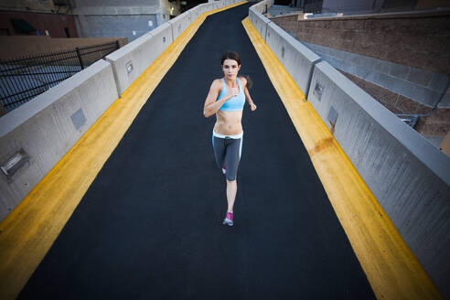 Caucasian woman running on city street - BLEF07425