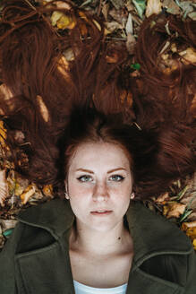 Young woman with long red hair lying amongst autumn leaves, overhead portrait - CUF51430