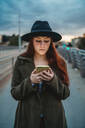 Young woman with long red hair on footbridge looking at smartphone at dusk - CUF51433