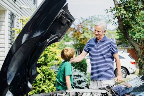 Caucasian grandfather and grandson repairing car in driveway - BLEF07546