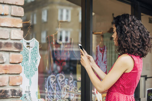 Mixed race woman taking cell phone photograph of clothes in store window - BLEF07570