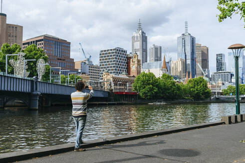 Man taking a picture  of cityscape of Melbourne with Yarra river, Victoria, Australia - KIJF02492