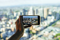 Close-up of man taking picture of the cityscape of Melbourne, Victoria, Australia - KIJF02495