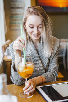 Young businesswoman using tablet in a bar - LJF00151