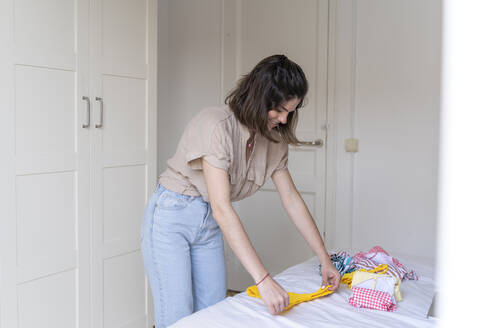 Young woman placing clothes on bed - AFVF03285