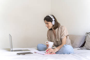 Young woman sitting on bed with headphones and laptop taking notes - AFVF03294