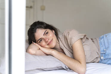 Smiling young woman lying on bed - AFVF03303