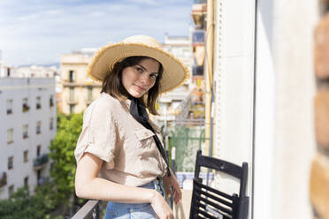 Portrait of smiling young woman wearing straw hat standing on balcony in the city - AFVF03312