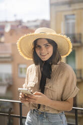 Portrait of smiling young woman wearing straw hat standing on balcony in the city - AFVF03315