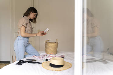 Young woman with notebook and summer fashion on bed - AFVF03321