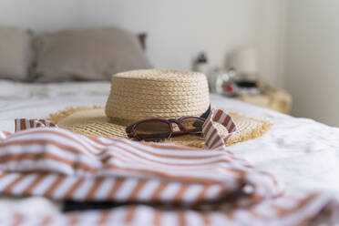 Bikini and straw hat lying on bed - AFVF03324