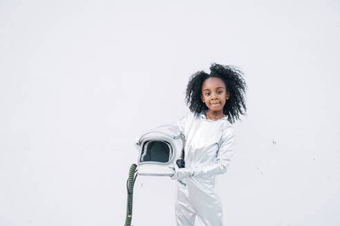 Portrait of little girl wearing space suit in front of white background - JCMF00063