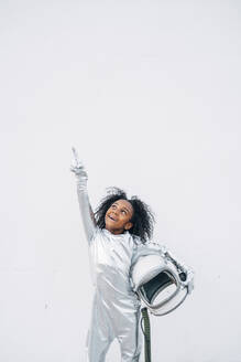 Portrait of smiling little girl wearing space suit in front of white background looking up - JCMF00066