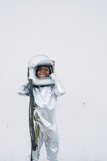 Smiling little girl wearing space suit putting on space hat in front of white background - JCMF00069