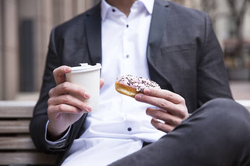 Businessman's hands holding doughnut and coffee to go, close-up - MFRF01314
