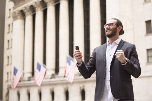 Happy young businessman with cell phone in front of Stock Exchange, New York City, USA - MFRF01320