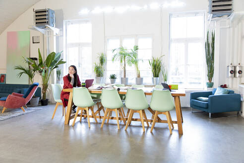 Woman working at table in modern office - FKF03340