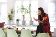 Woman using cell phone in modern office - FKF03349