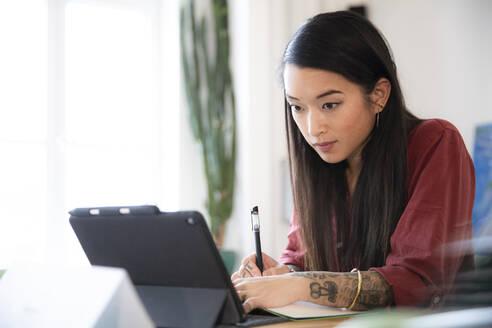 Woman using tablet in office - FKF03361