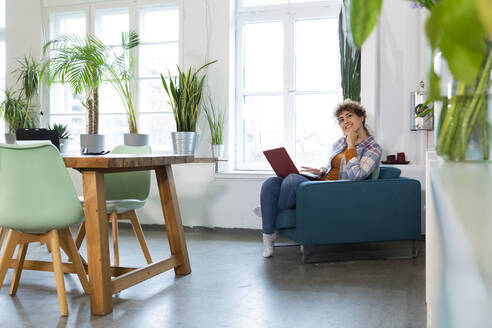 Smiling woman using laptop in armchair in office - FKF03373