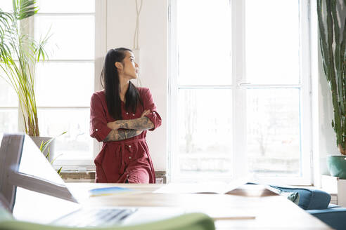Woman looking out of window in office - FKF03388