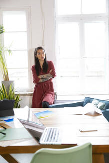 Portrait of confident woman at the window in office - FKF03391