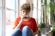 Portrait of woman drinking coffee at the window in office - FKF03397