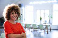 Portrait of smiling woman in modern office - FKF03418