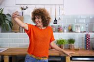 Happy woman taking a selfie in office kitchen - FKF03424