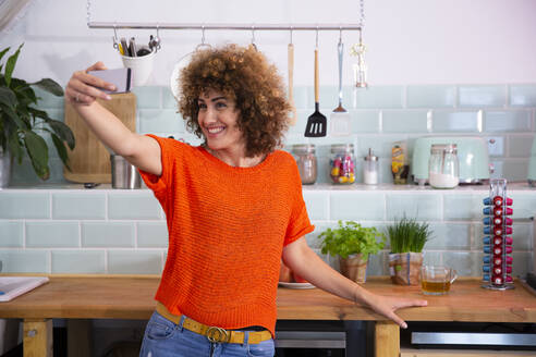 Happy woman taking a selfie in office kitchen - FKF03424