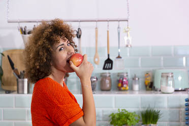 Portrait of woman eating an apple in office kitchen - FKF03427