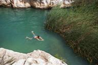Man swimming in a small lake at Wadi Shab, Oman - WWF05137