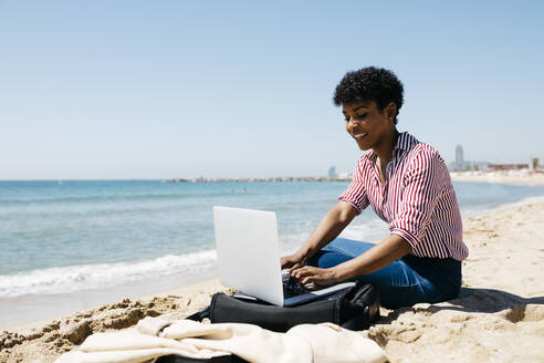 Woman sitting on the beach while working with the laptop - JRFF03319