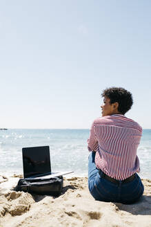Woman sitting on the beach while working with the laptop - JRFF03322