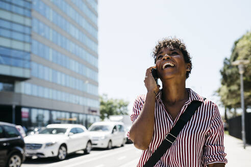 Woman talking on the phone while walking in the city - JRFF03328