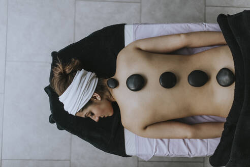 Young woman with heated stones on her back - OCAF00419