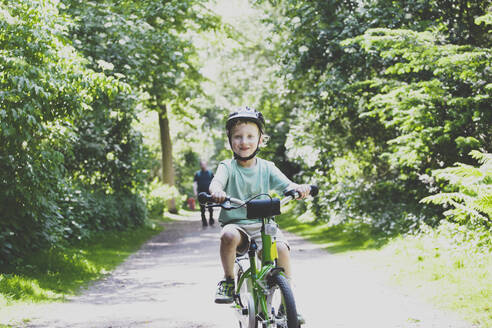 Portrait of proud little boy learning to ride bicycle - IHF00143