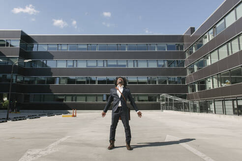 Businessman standing outside office with outstretched arms - AHSF00528