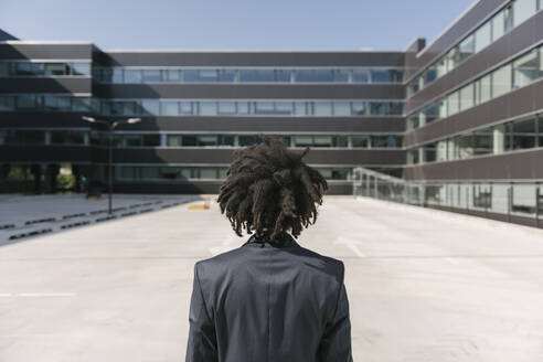 Rear view of businessman with dreadlocks standing outside office - AHSF00531