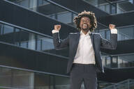 Excited businessman cheering outside office - AHSF00561