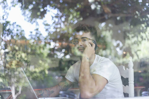 Young man with laptop on cell phone behind windowpane of a cafe - JPTF00160