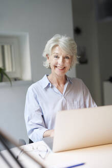 Portrait of smiling mature woman using laptop at desk - PNEF01699