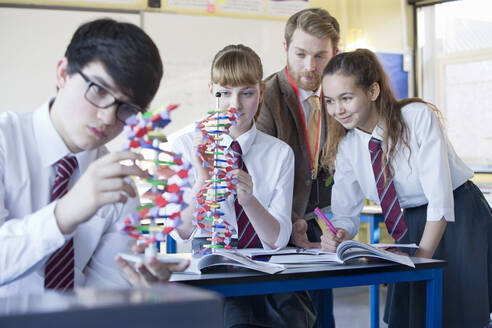 High school students assembling helix DNA model in science class - JUIF01585