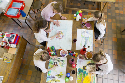 Art teacher guiding middle school students painting in art class - JUIF01588