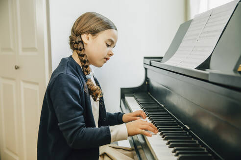 Mixed race girl playing piano - BLEF07781
