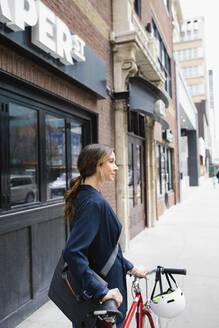 Businesswoman walking bicycle on urban sidewalk - HEROF36648
