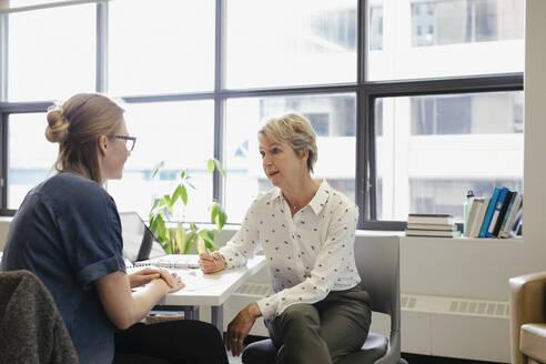Businesswomen talking in office - HEROF36663