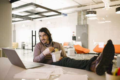 Businessman with feet up using laptop and eating take out food in conference room - HEROF36747