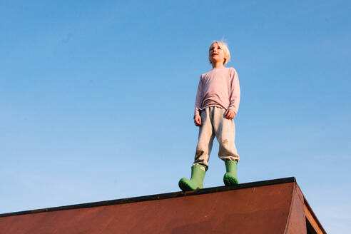 Boy standing on top of skateboard ramp against blue sky, low angle view - ISF21578